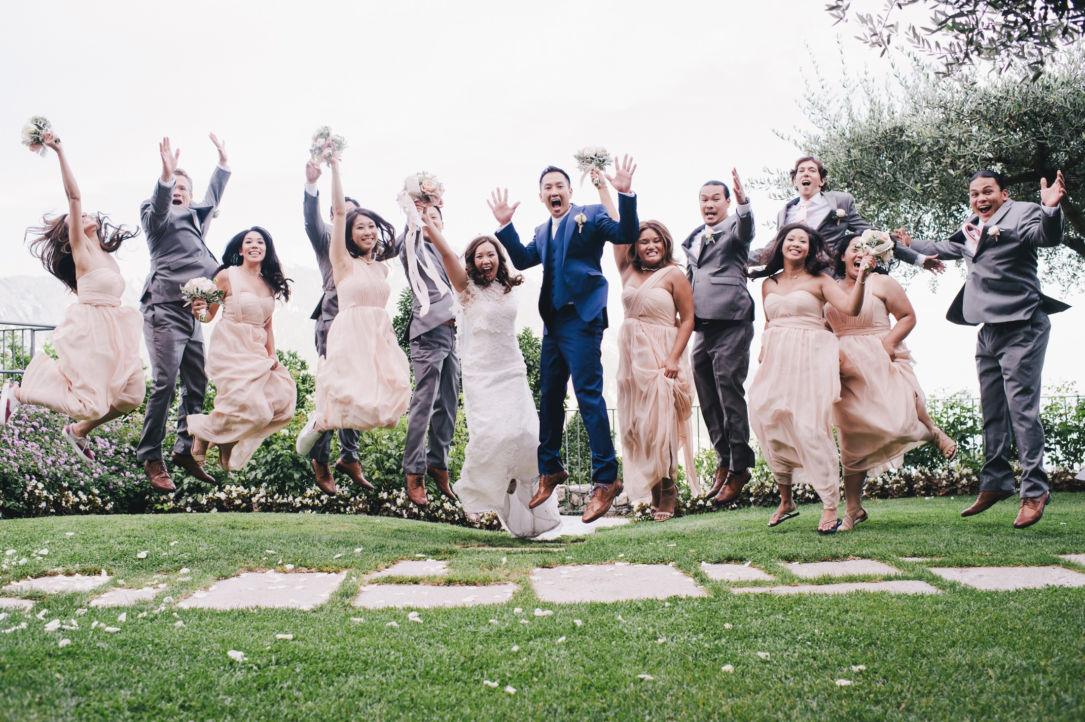 bride and groom jumping together with all they best men and bridesmaids