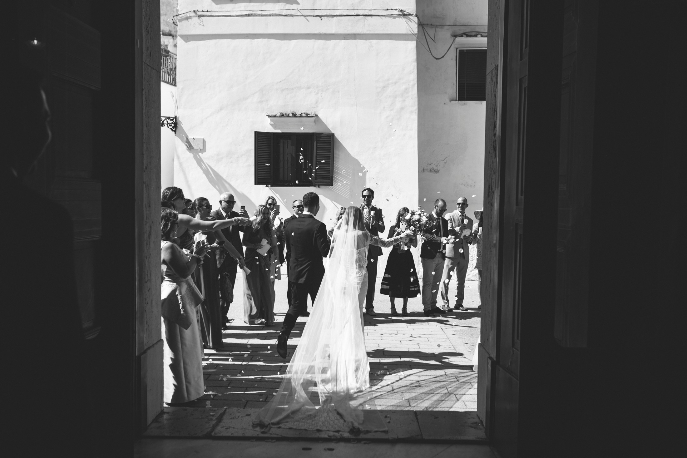 bride and groom leave the church black and white