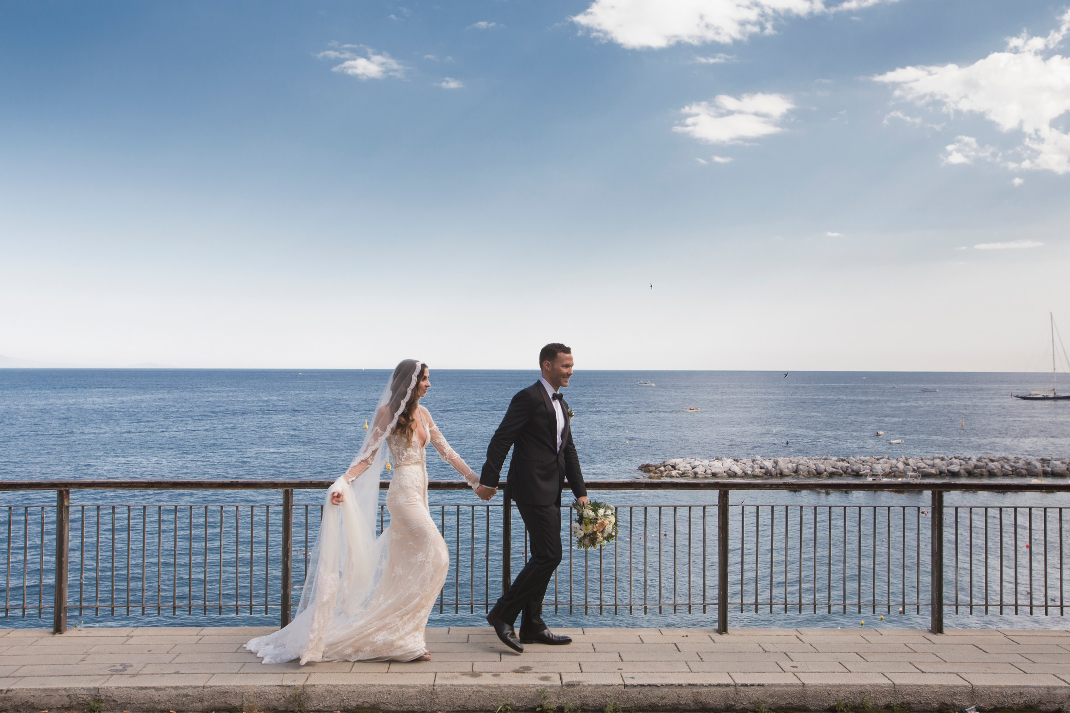 bride and groom walking together with the sea on the background