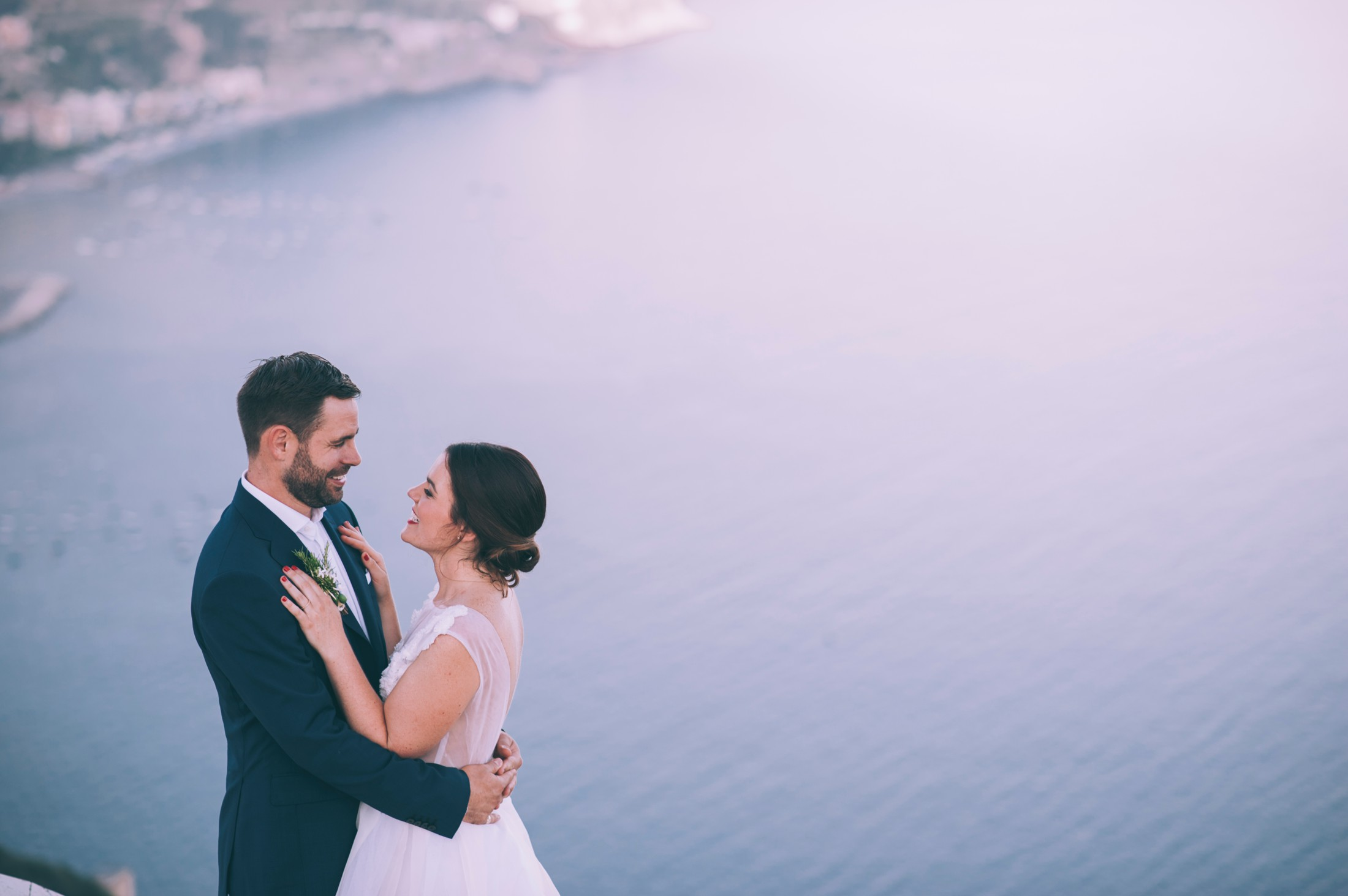 bride and groom holding each other with the sea as background