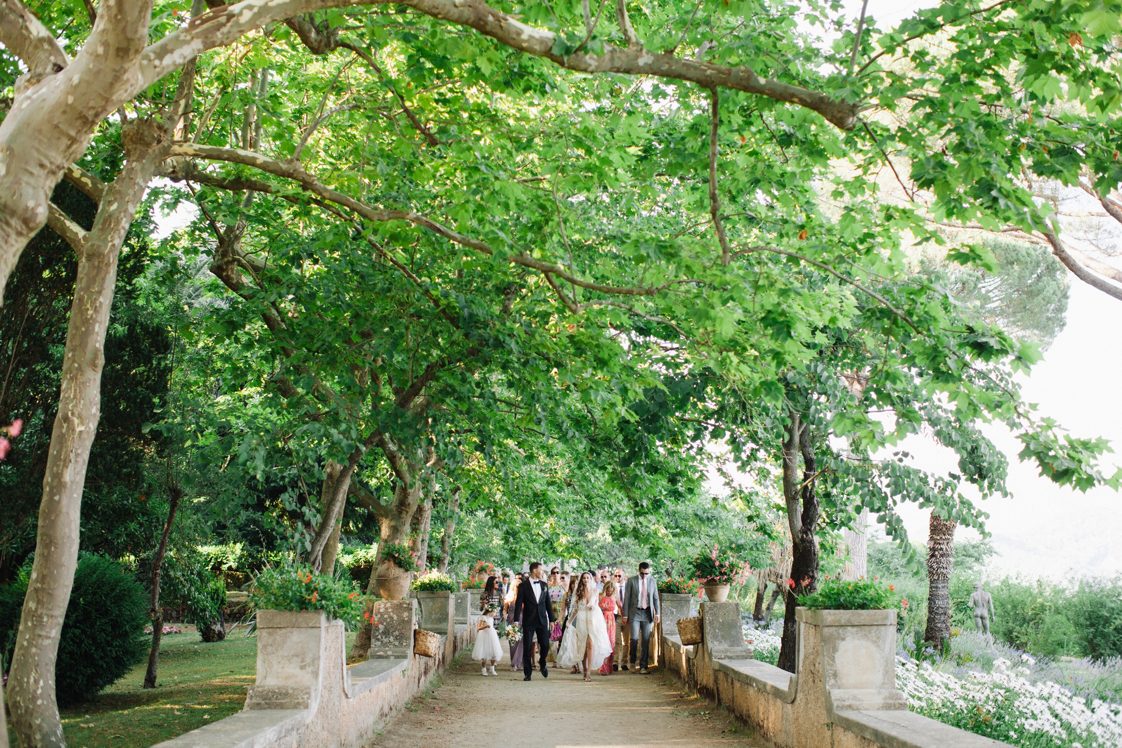 the bride and the groom walk through villa cimbrone gardens followed by their wedding guests