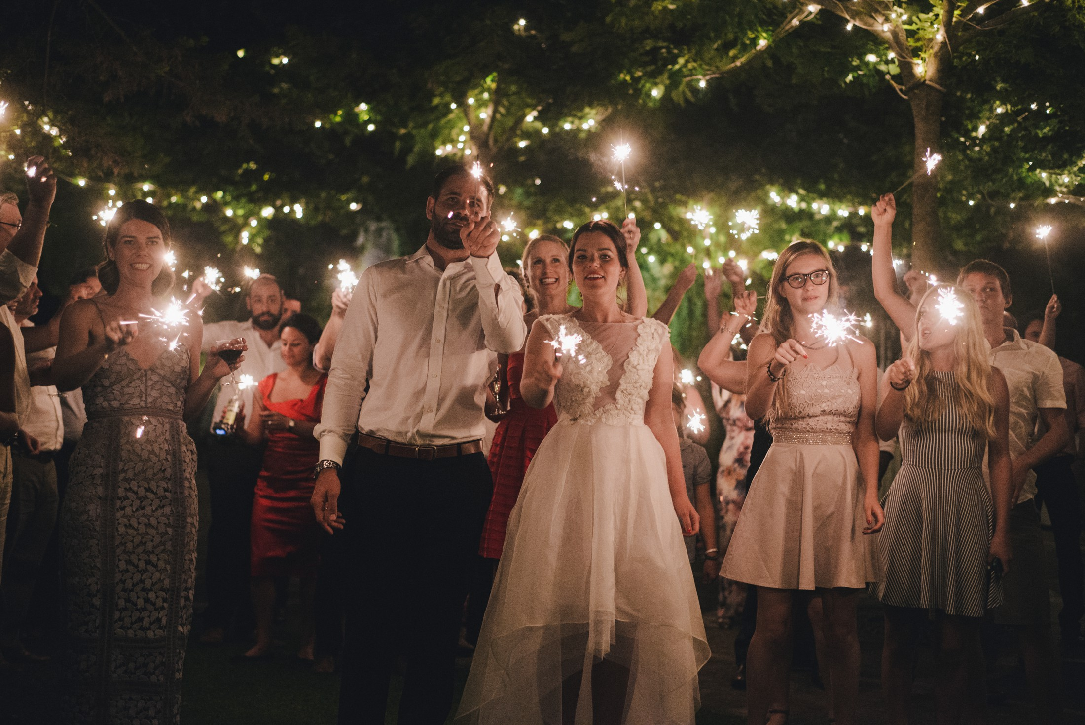 bride and groom with all the guests holding sparkles