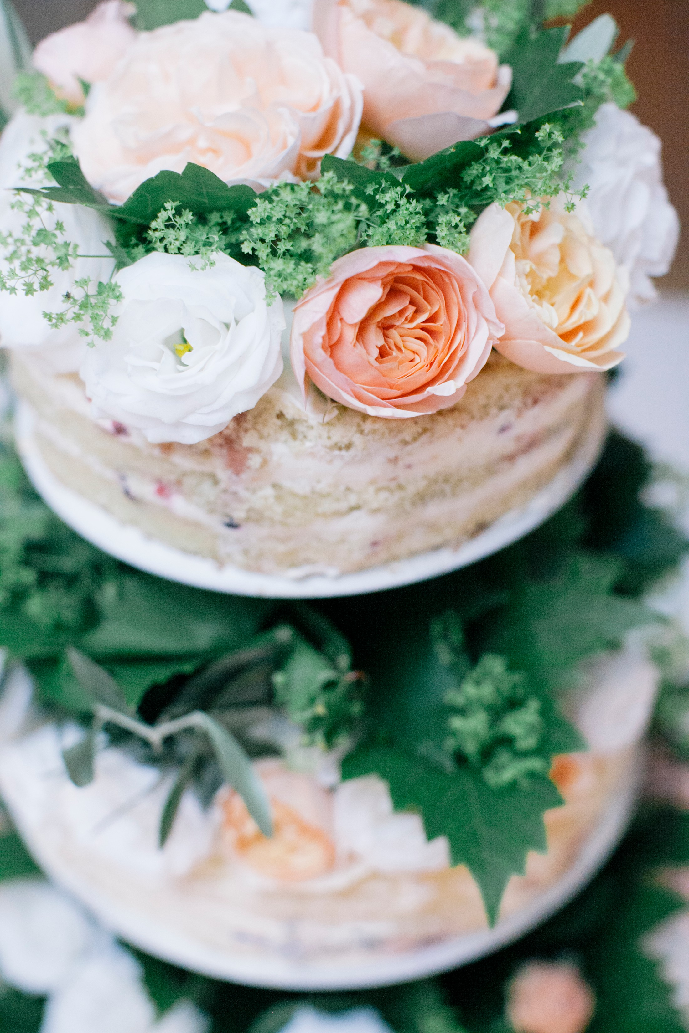 wedding cake with green leaves, orange and white flowers