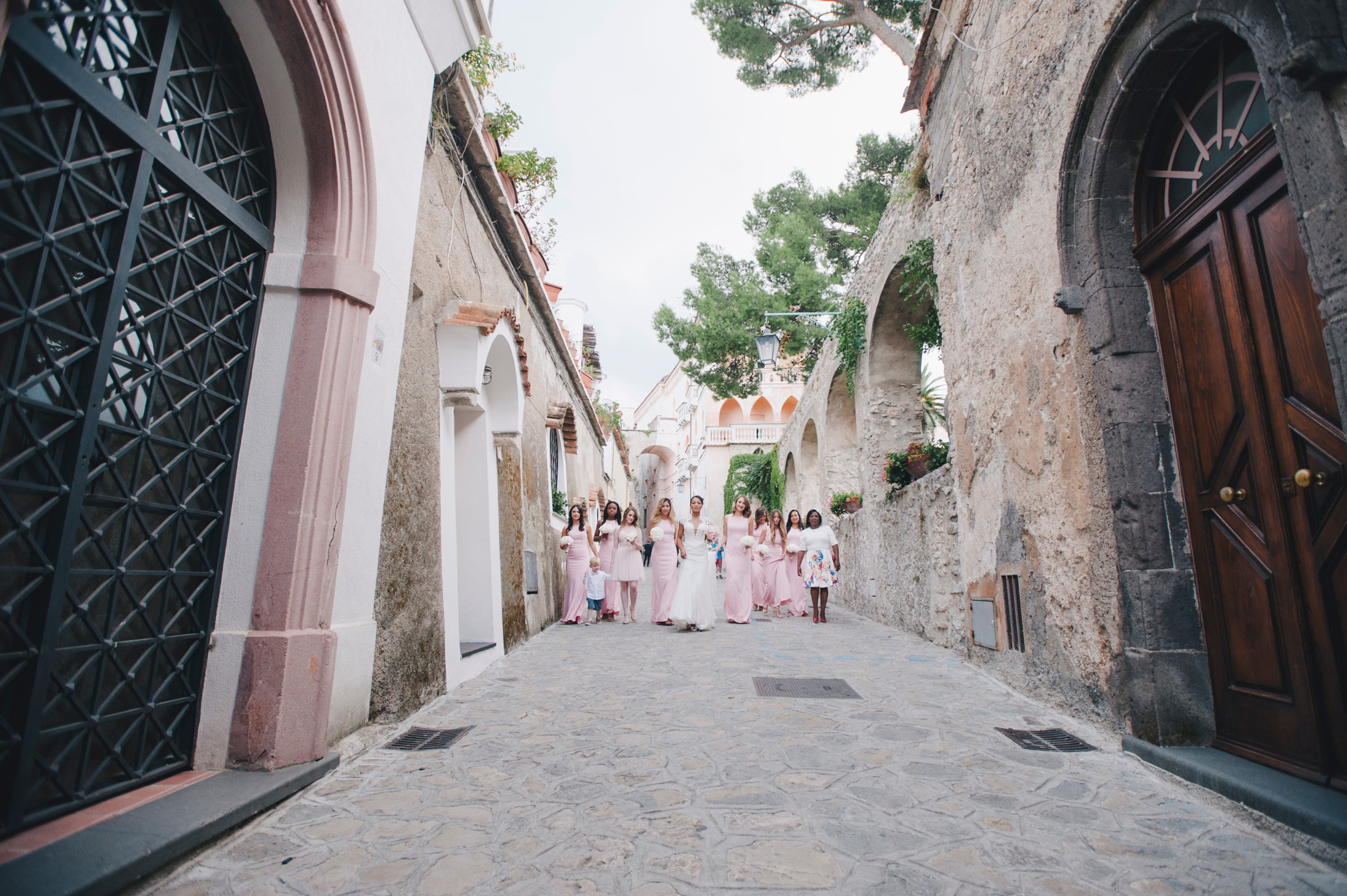 bride with bridesmaids walking to the wedding ceremony