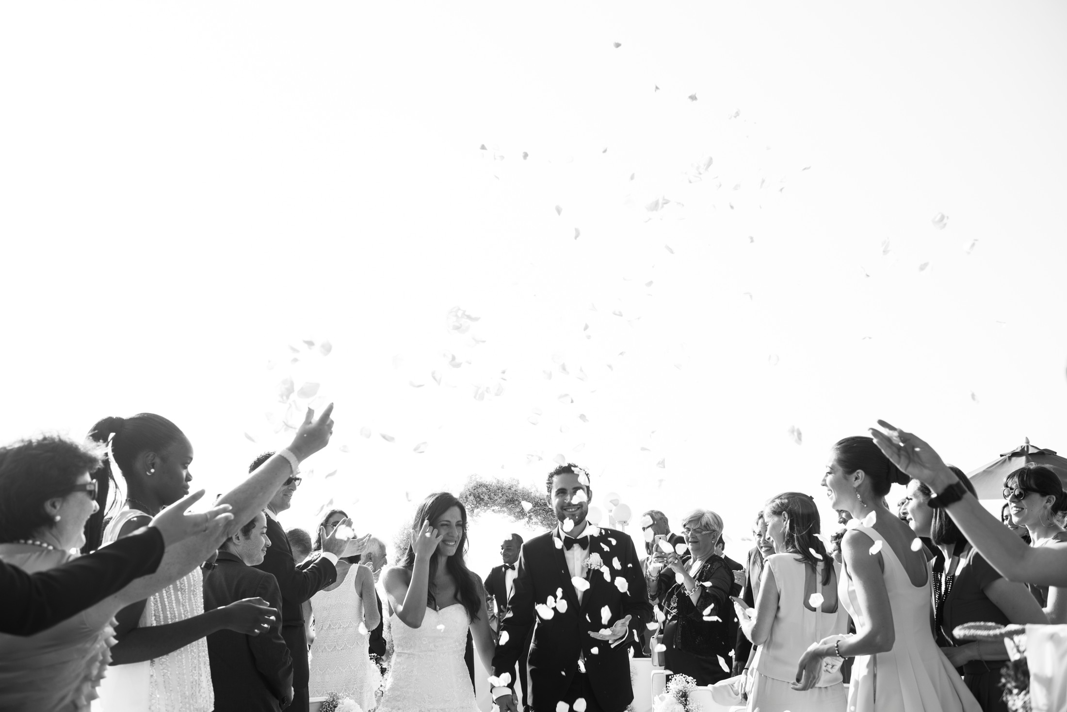 bride and groom after the wedding ceremony with guests throwing white petals
