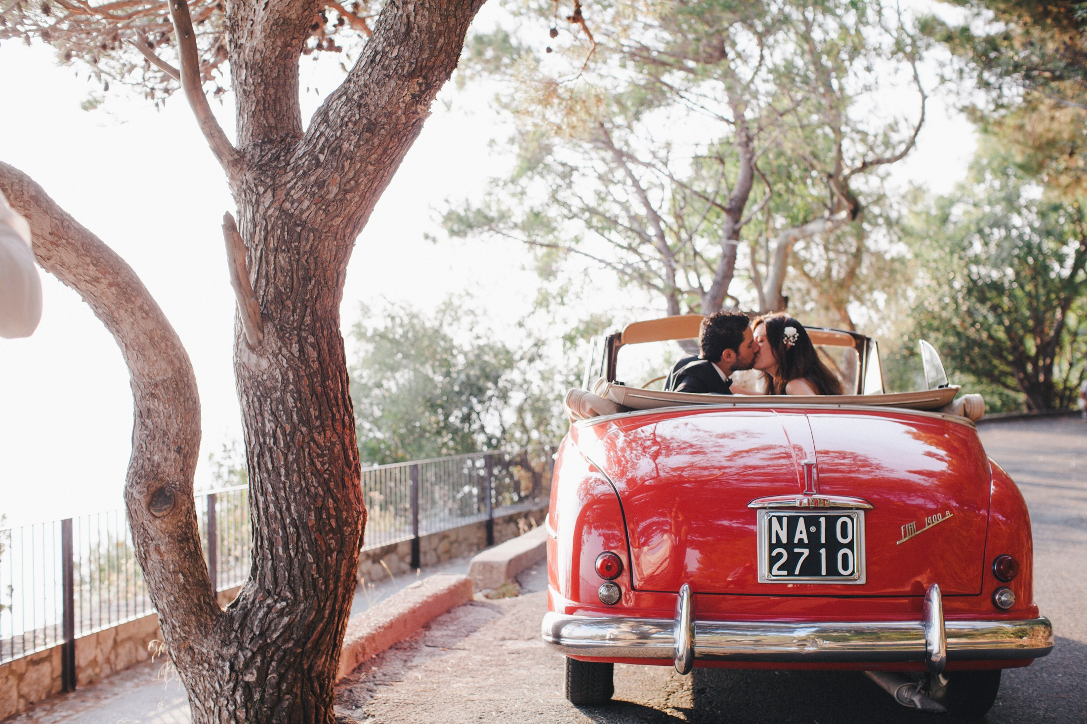 bride and groom kissing in their red wedding car