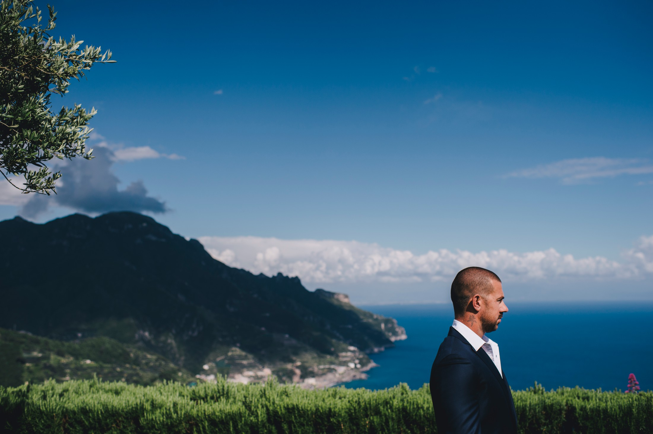 groom's portrait with the view of the coast on the background