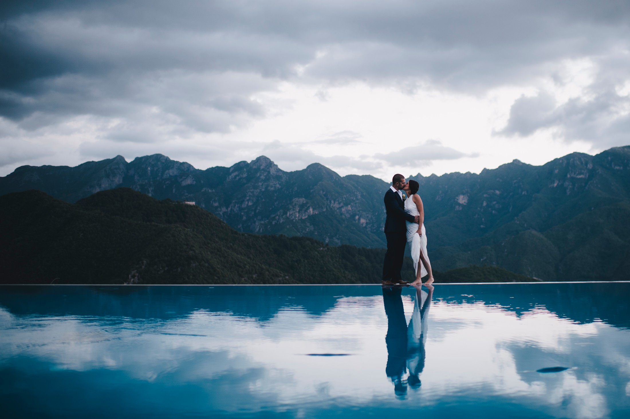bride and groom kissing at the infinity pool of the hotel caruso in ravello