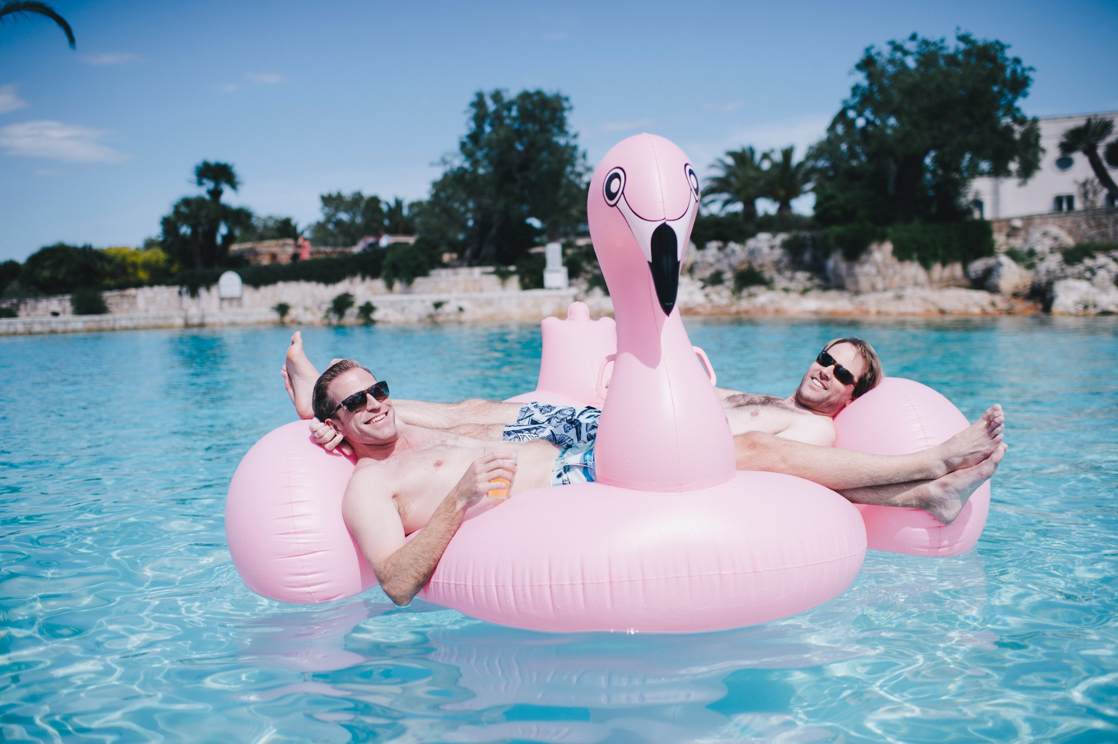 wedding guests relaxing on pink swans in the water