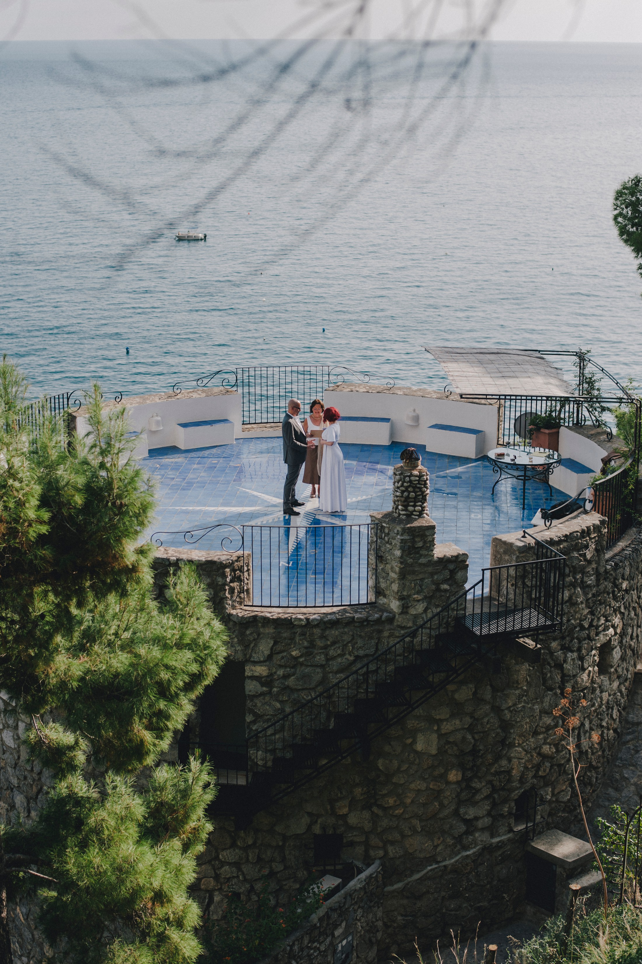 the bride, the groom and the celebrant during the civil wedding ceremony on a terrace in positano