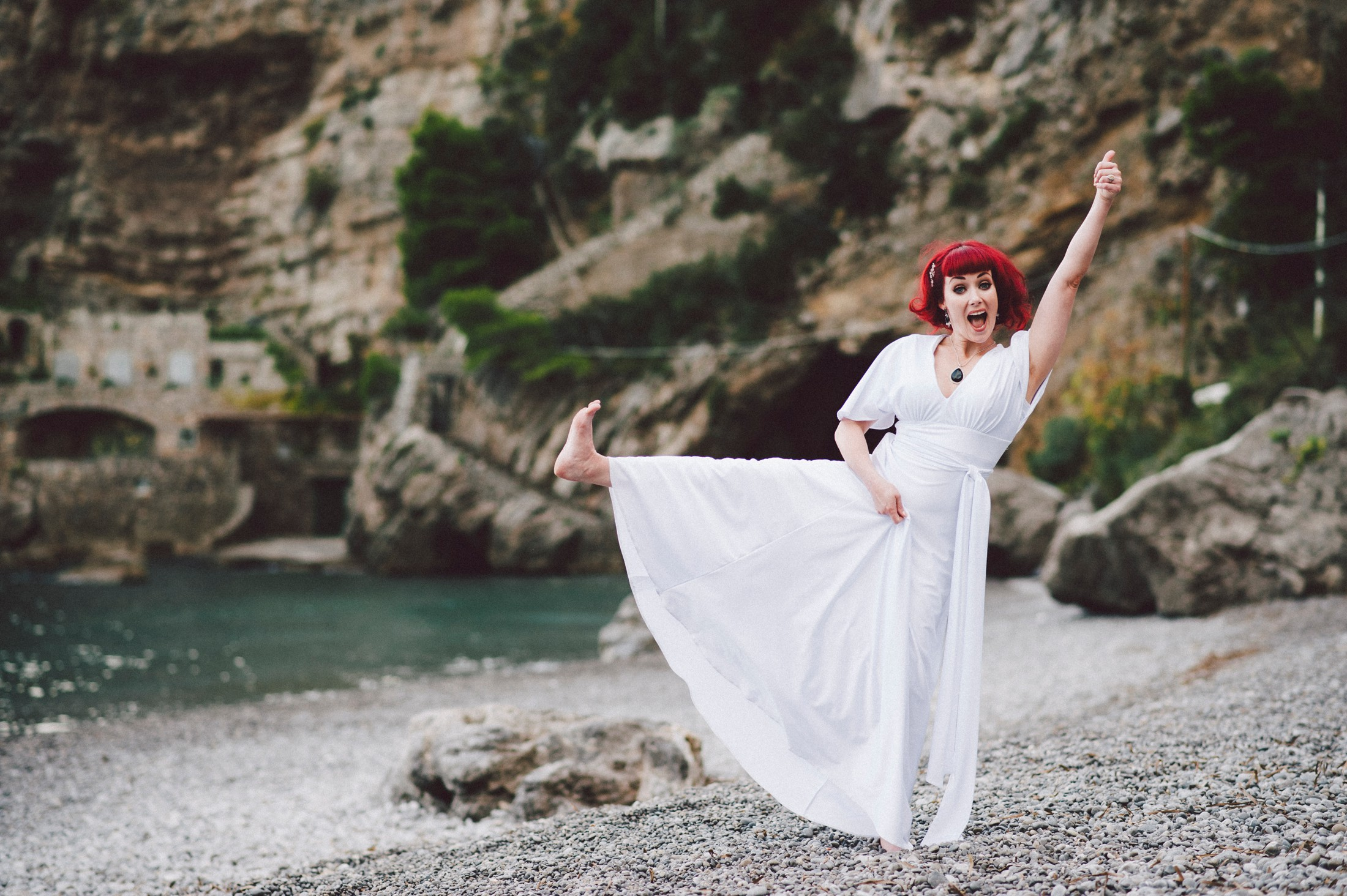 bride in a funny pose on the beach of positano