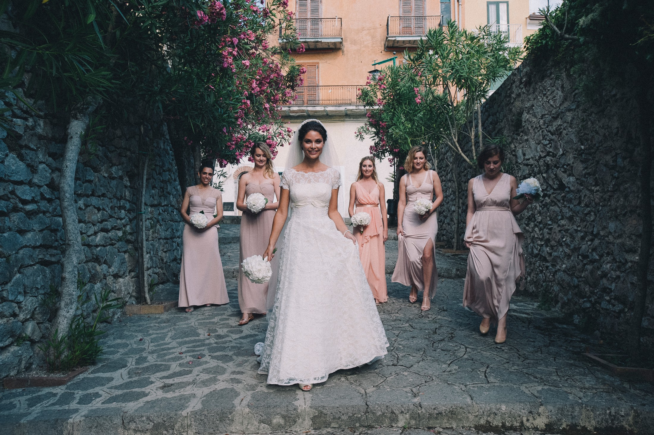 the bride walks with her bridesmaids to the wedding ceremony