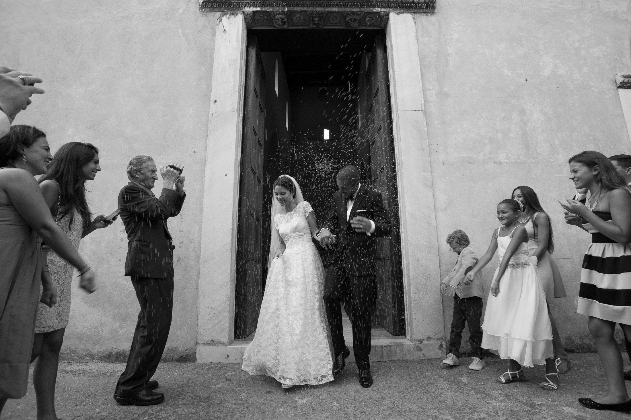 bride and groom leaving the church while guests throw rise