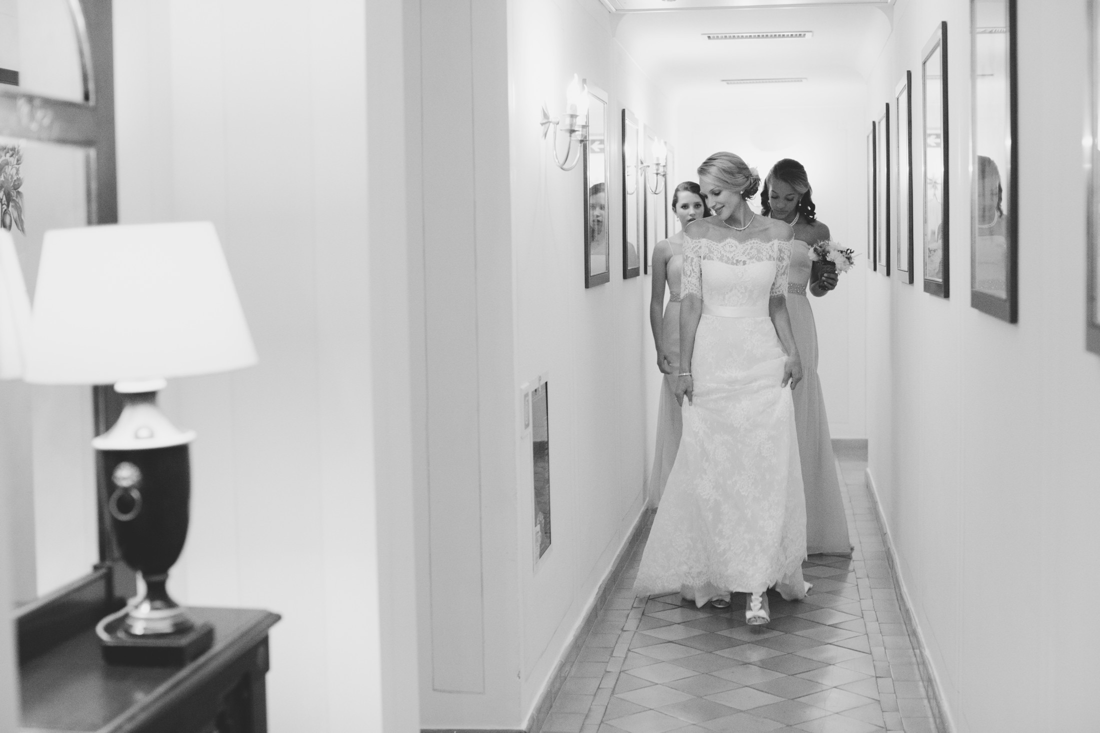 the bride with her two daughters leaving the hotel room in black and white