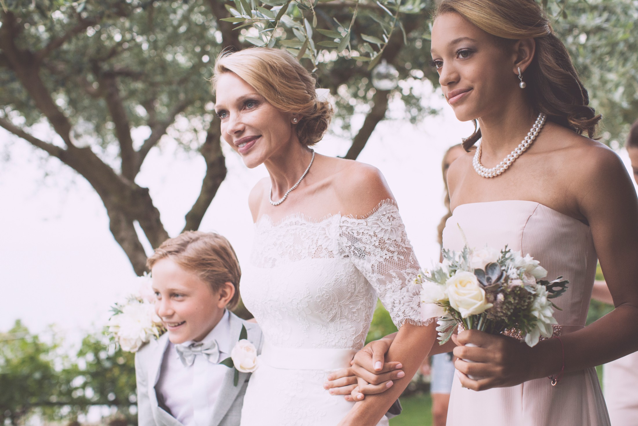 the bride walking with her son and her mother