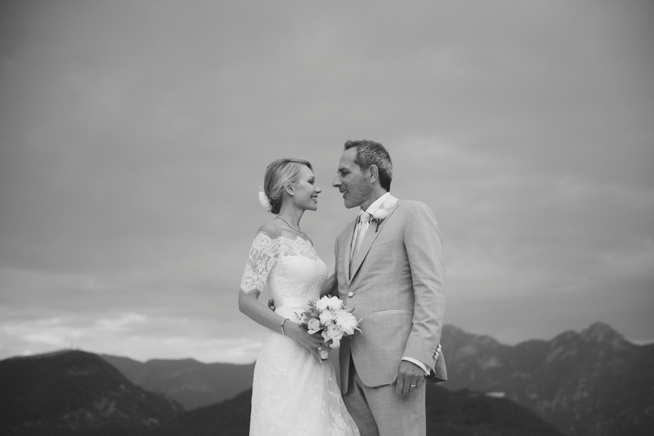 black and white groom and bride's portrait with mountains on the background