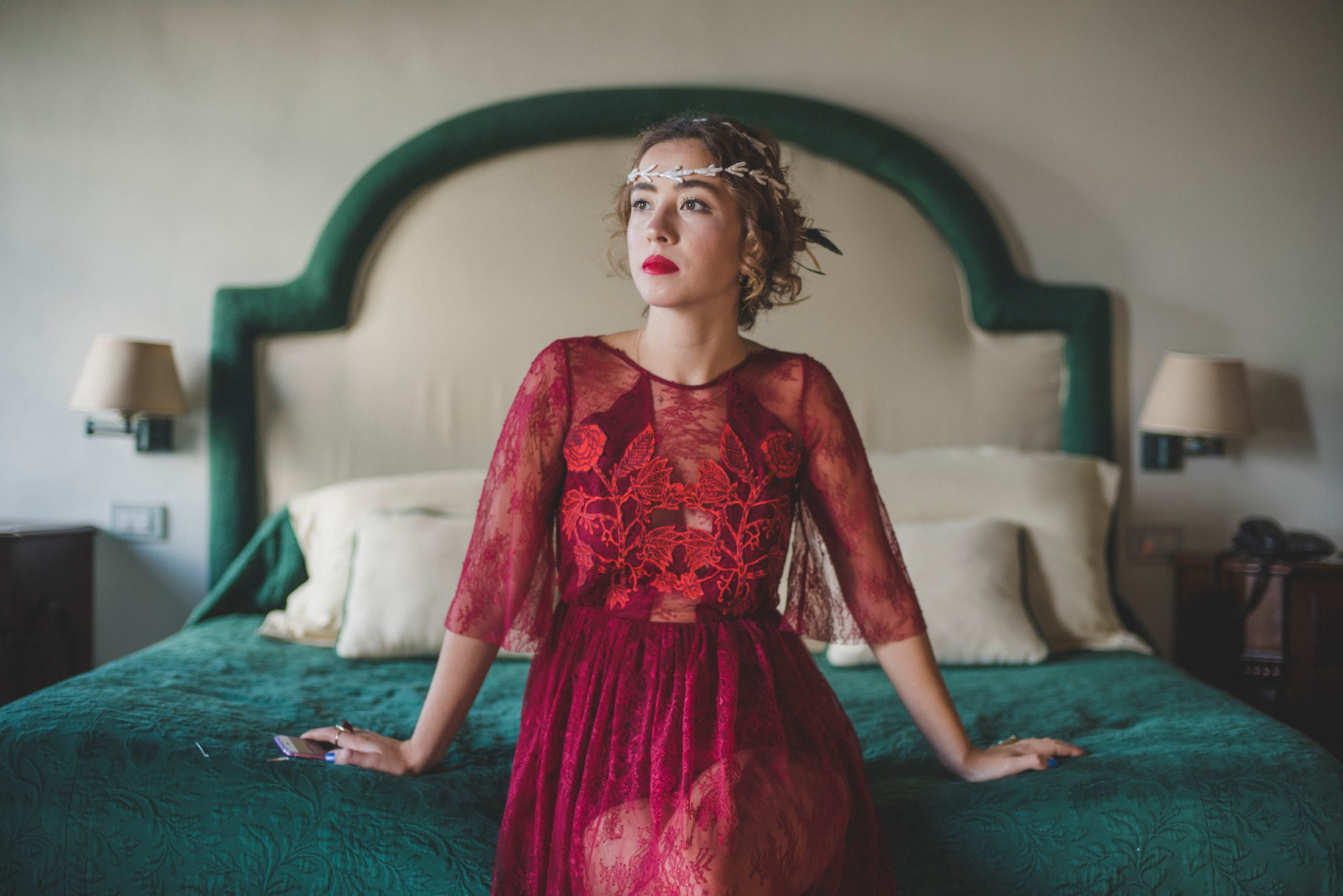 woman in a red dress sitting on the bed