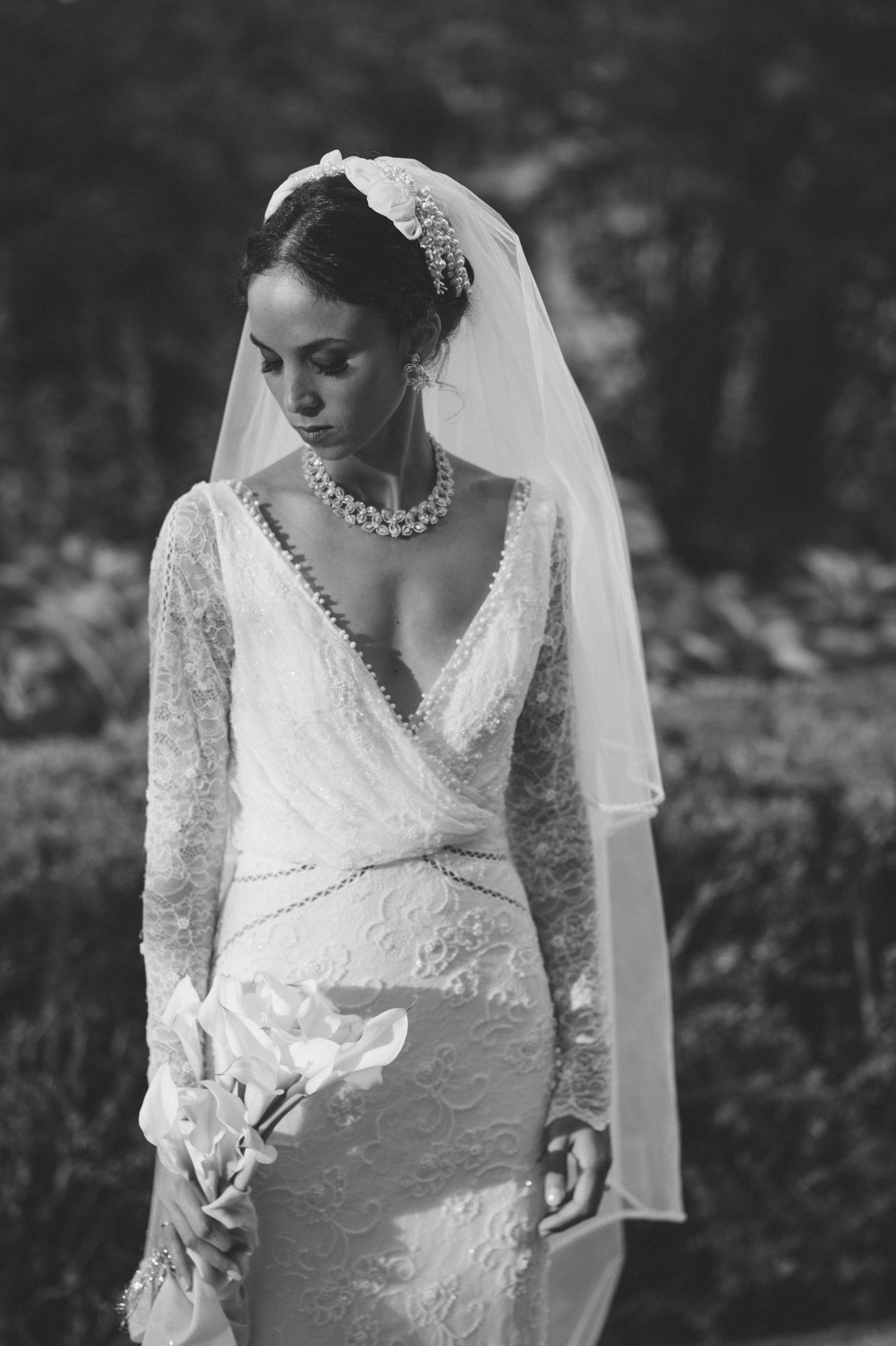 bride looking at her bouquet in black and white