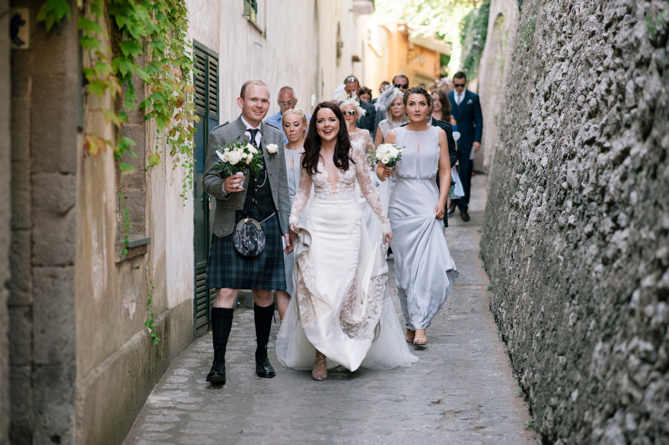 bride and groom with their wedding guests walking to villa cimbrone ravello