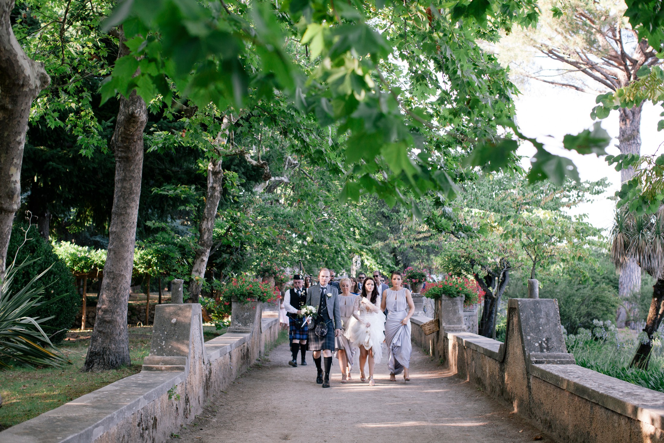 bride and groom with their wedding guests walking through villa cimbrone gardens in ravello
