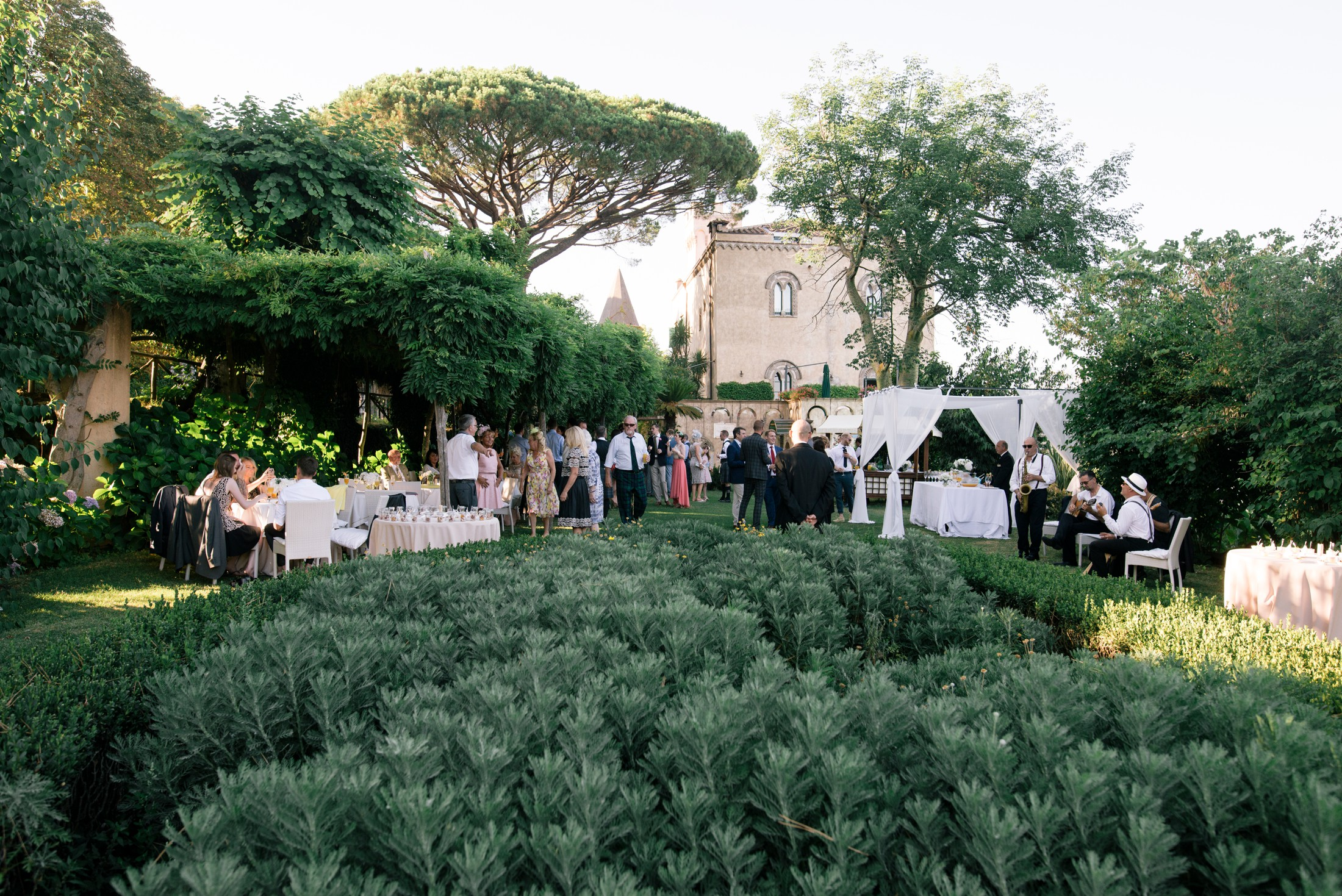 wedding guests drinking and talking together at villa cimbrone ravello