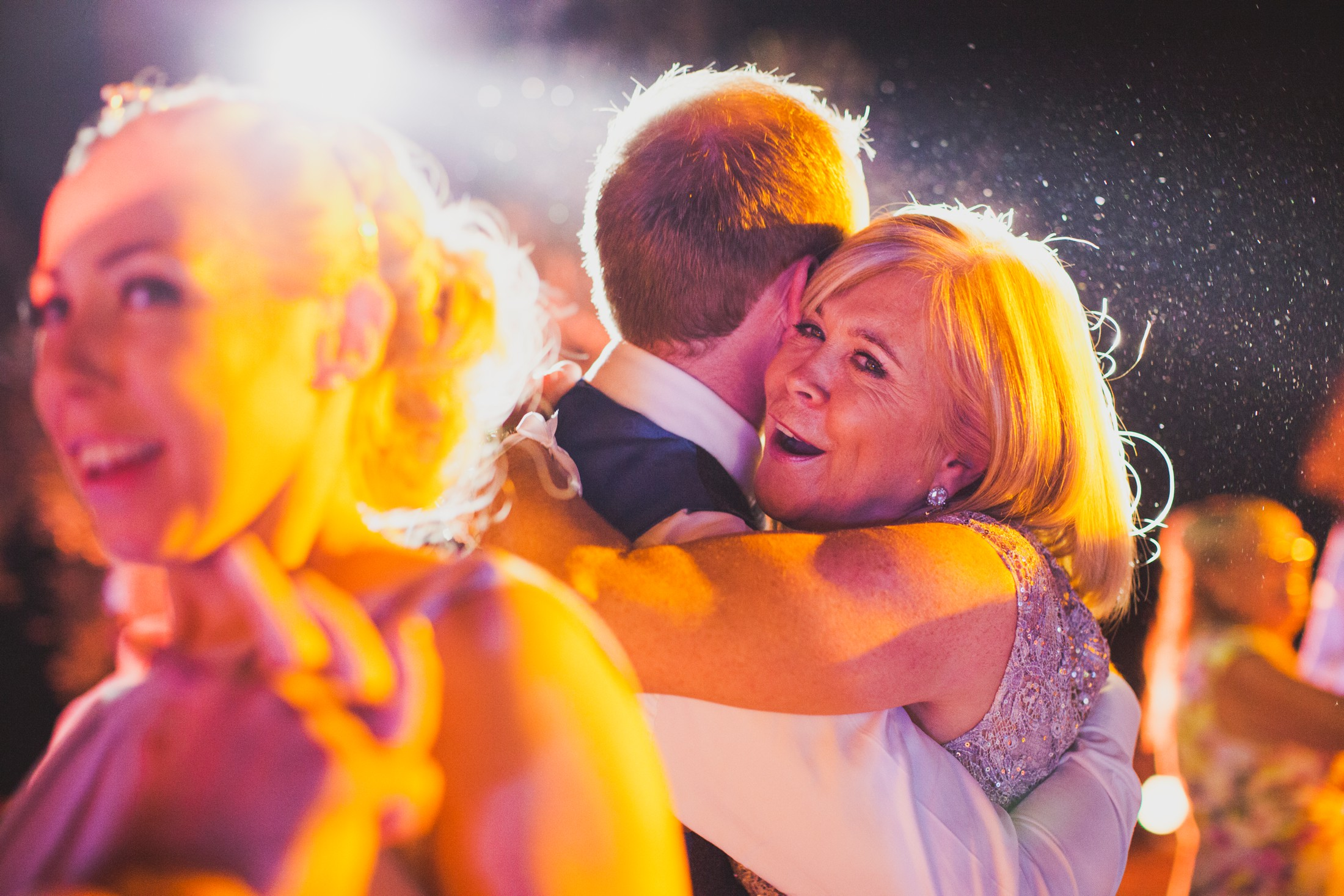 the groom's mother hold his son during the wedding dance party at villa cimbrone ravello