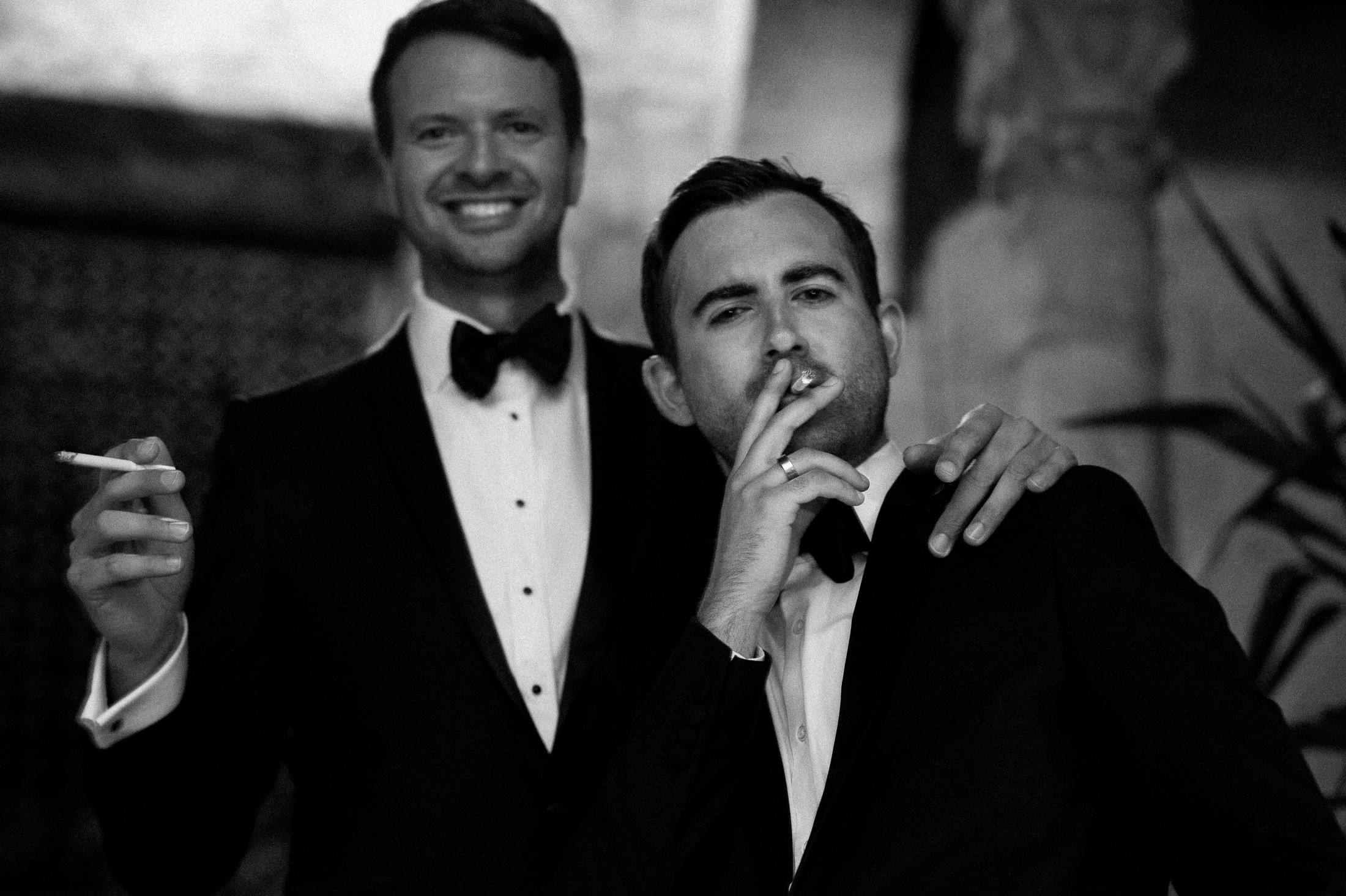two wedding guests smoking a cigarette