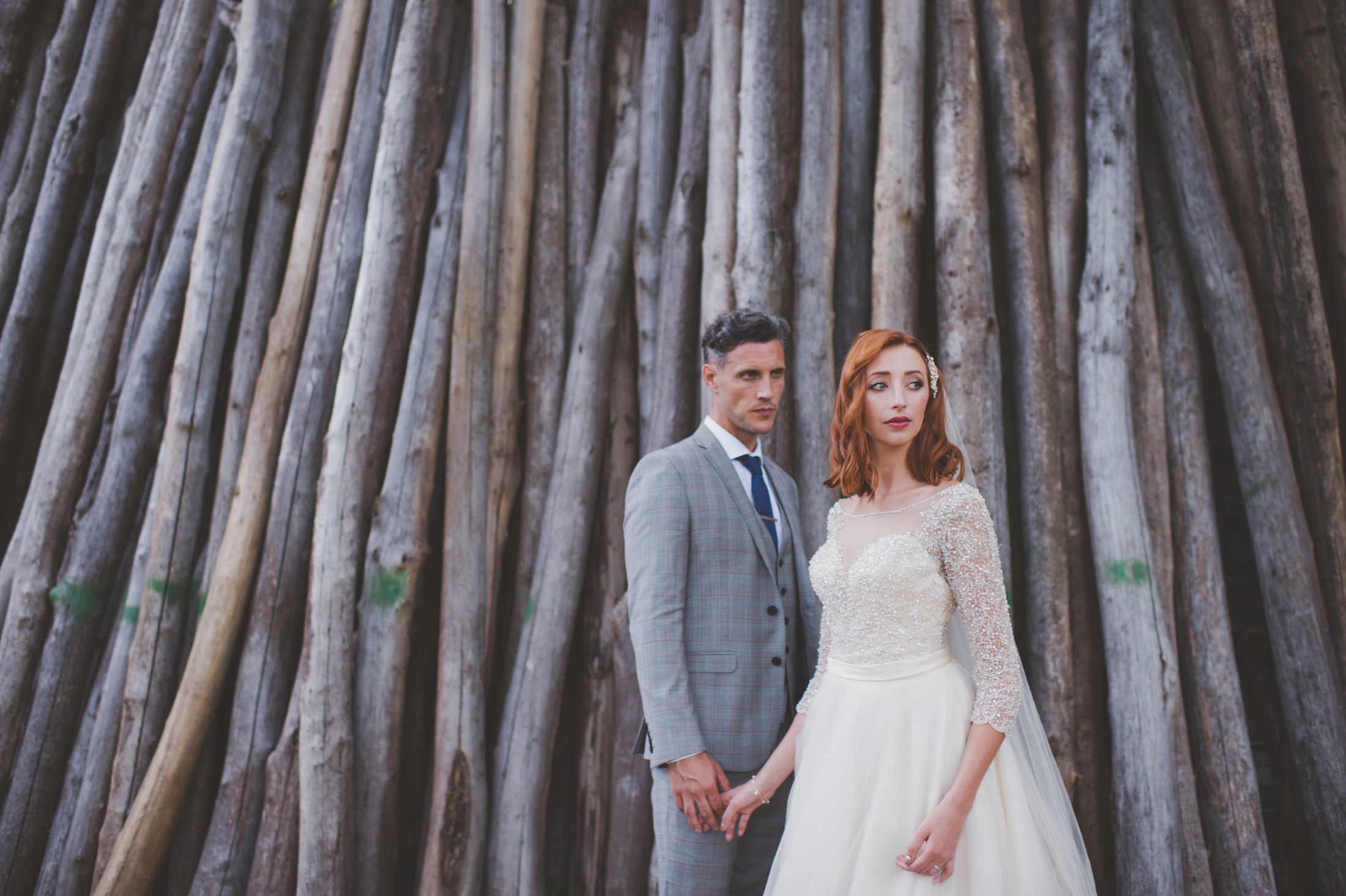 bride and groom's portrait standing by woods