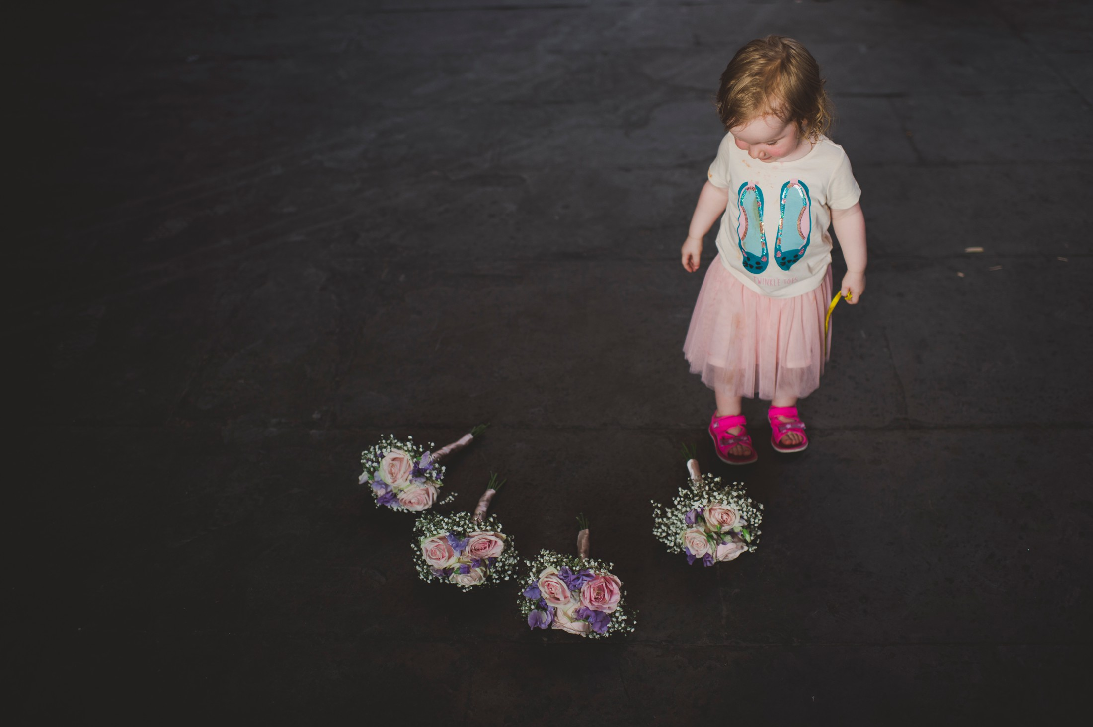 baby girl with bridesmaids bouquet on the floor