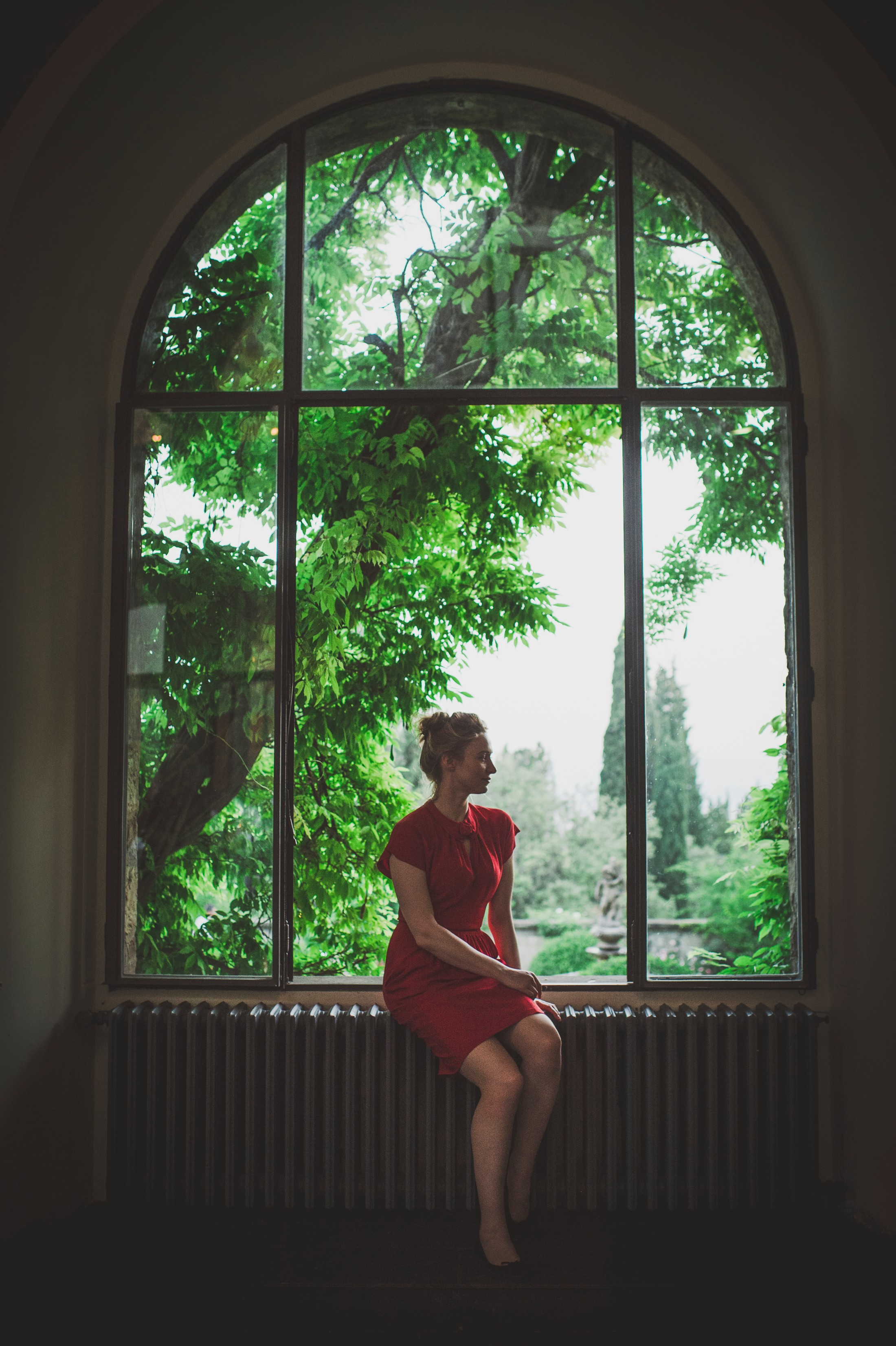 woman with red dress at the window