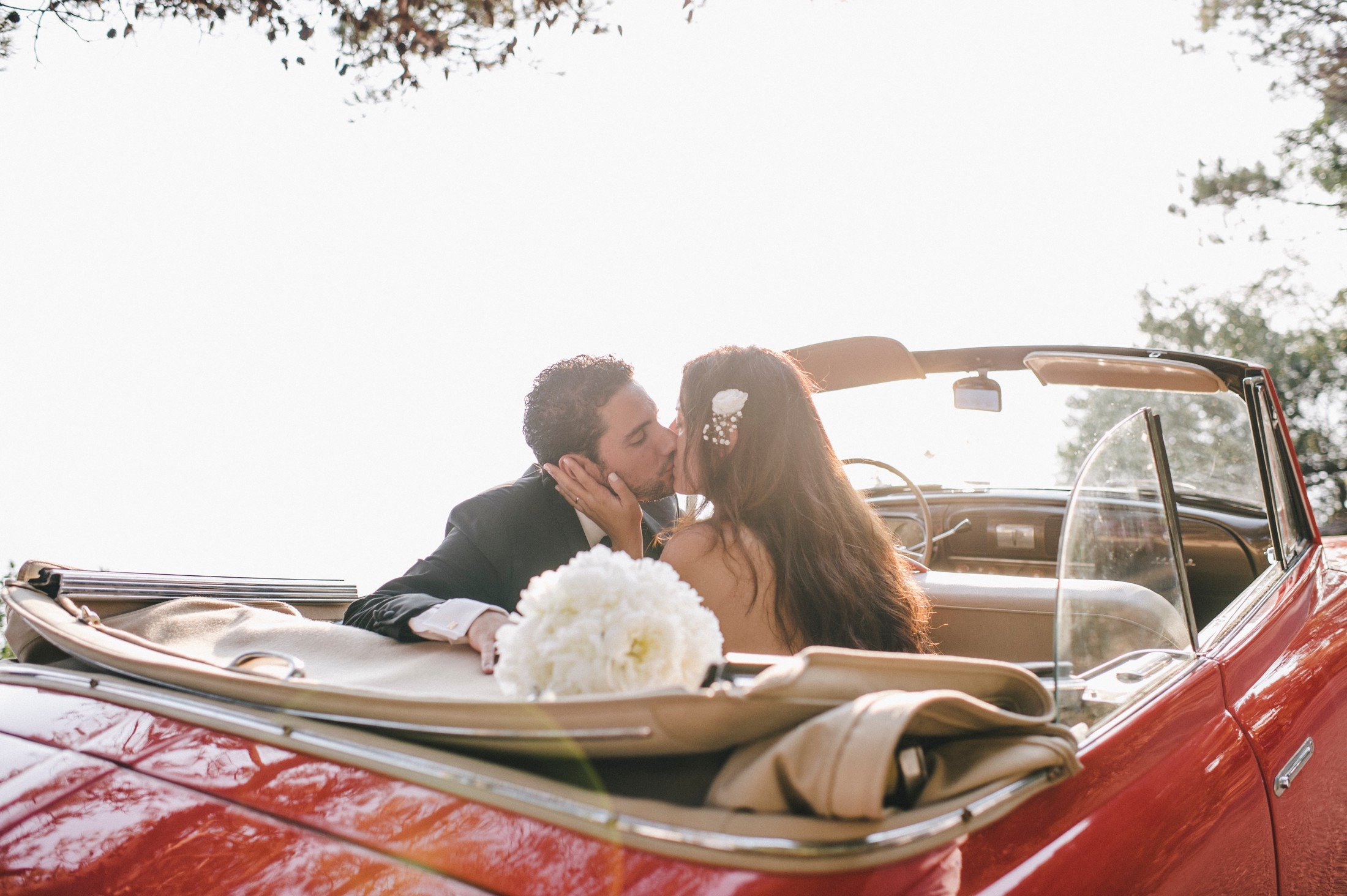 the bride and the groom kissing in their wedding car