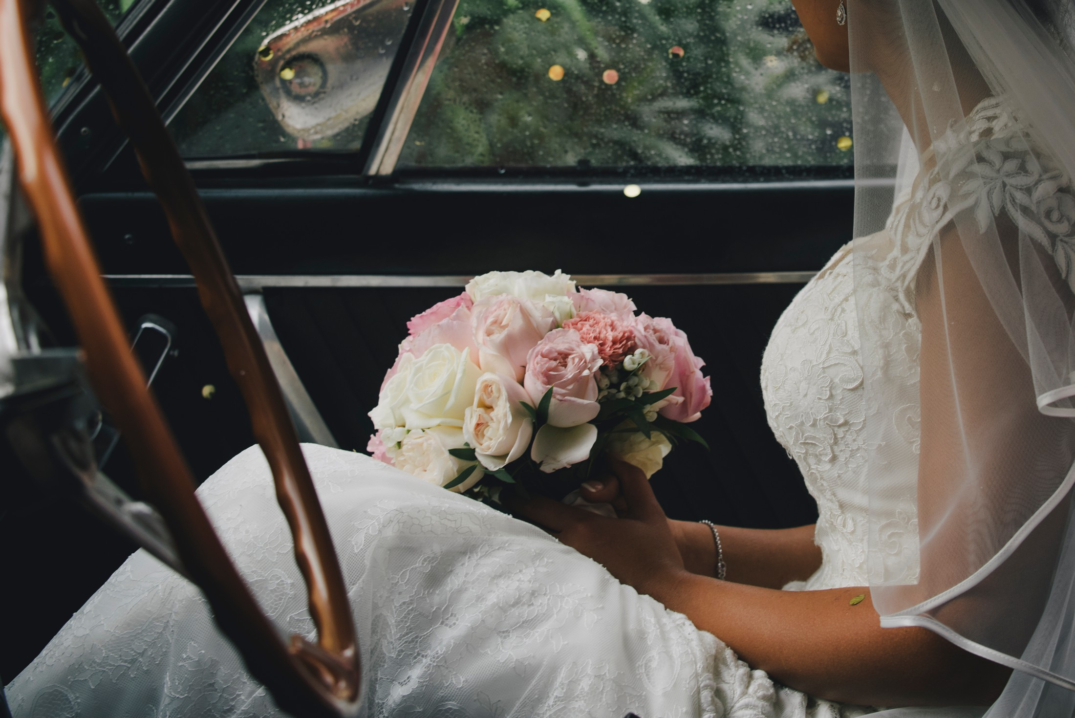 the bride sitting in the wedding car with the bouquet