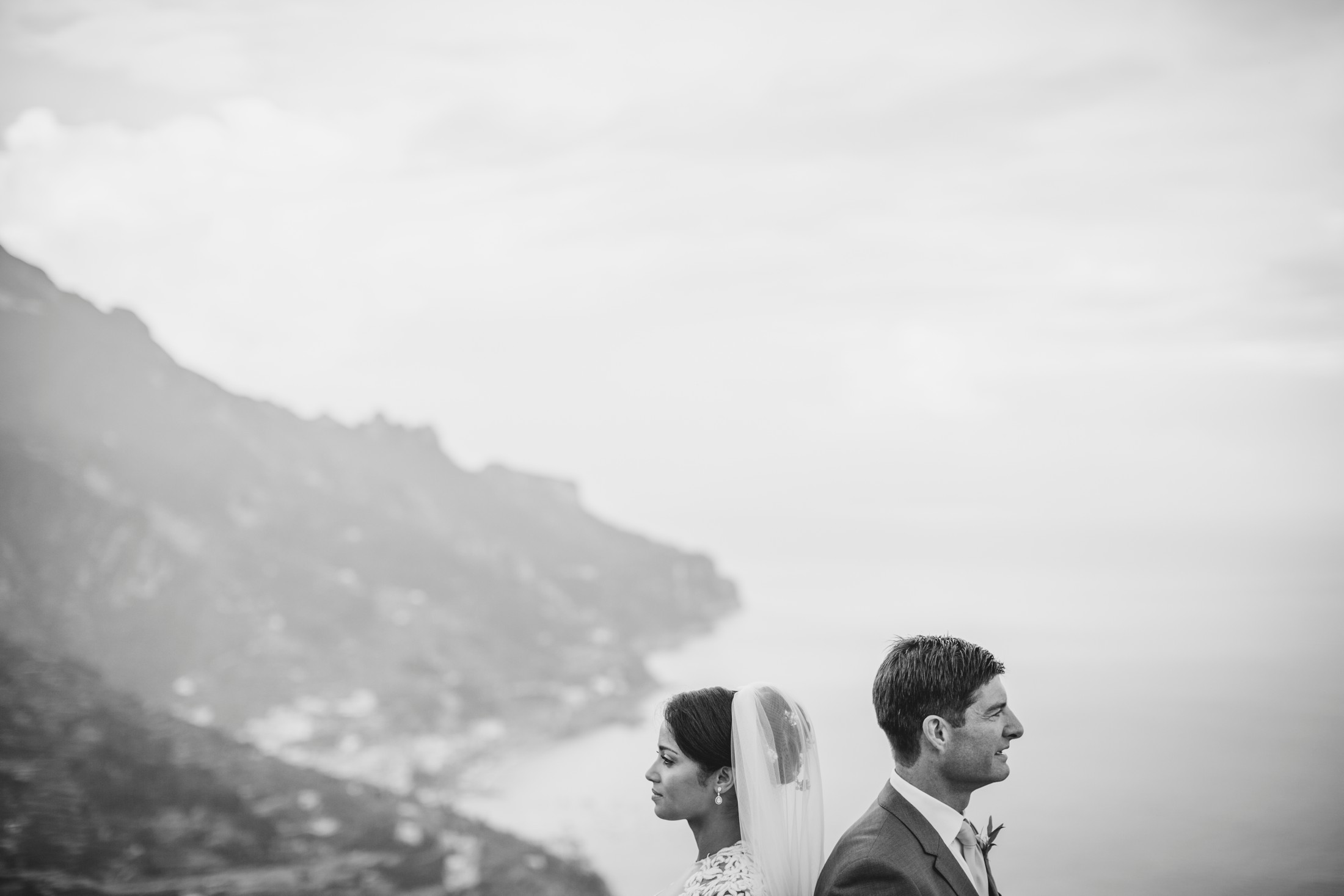 bride and groom's portrait in black and white with mountains on the back