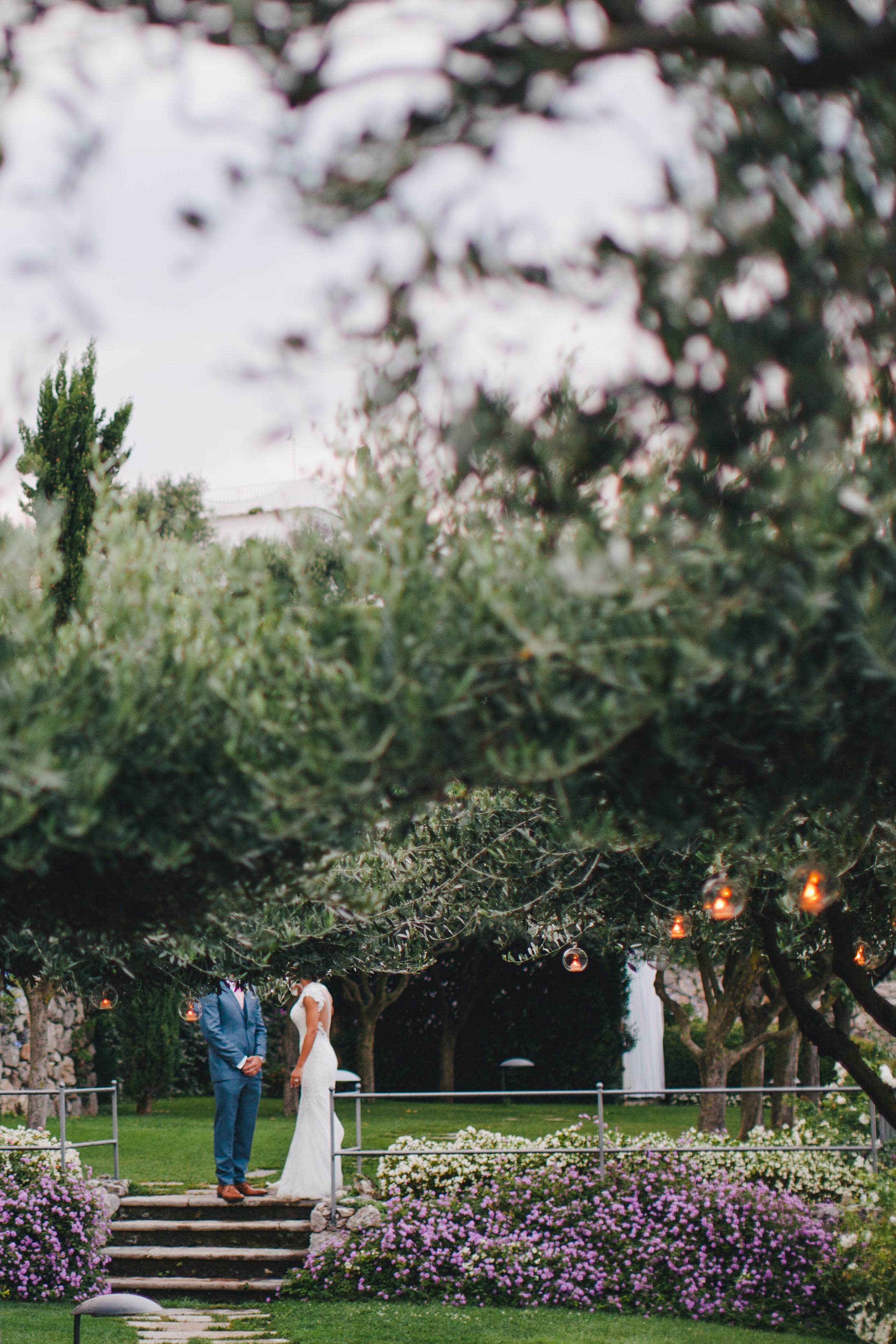 bride and groom behind the trees at caruso hotel