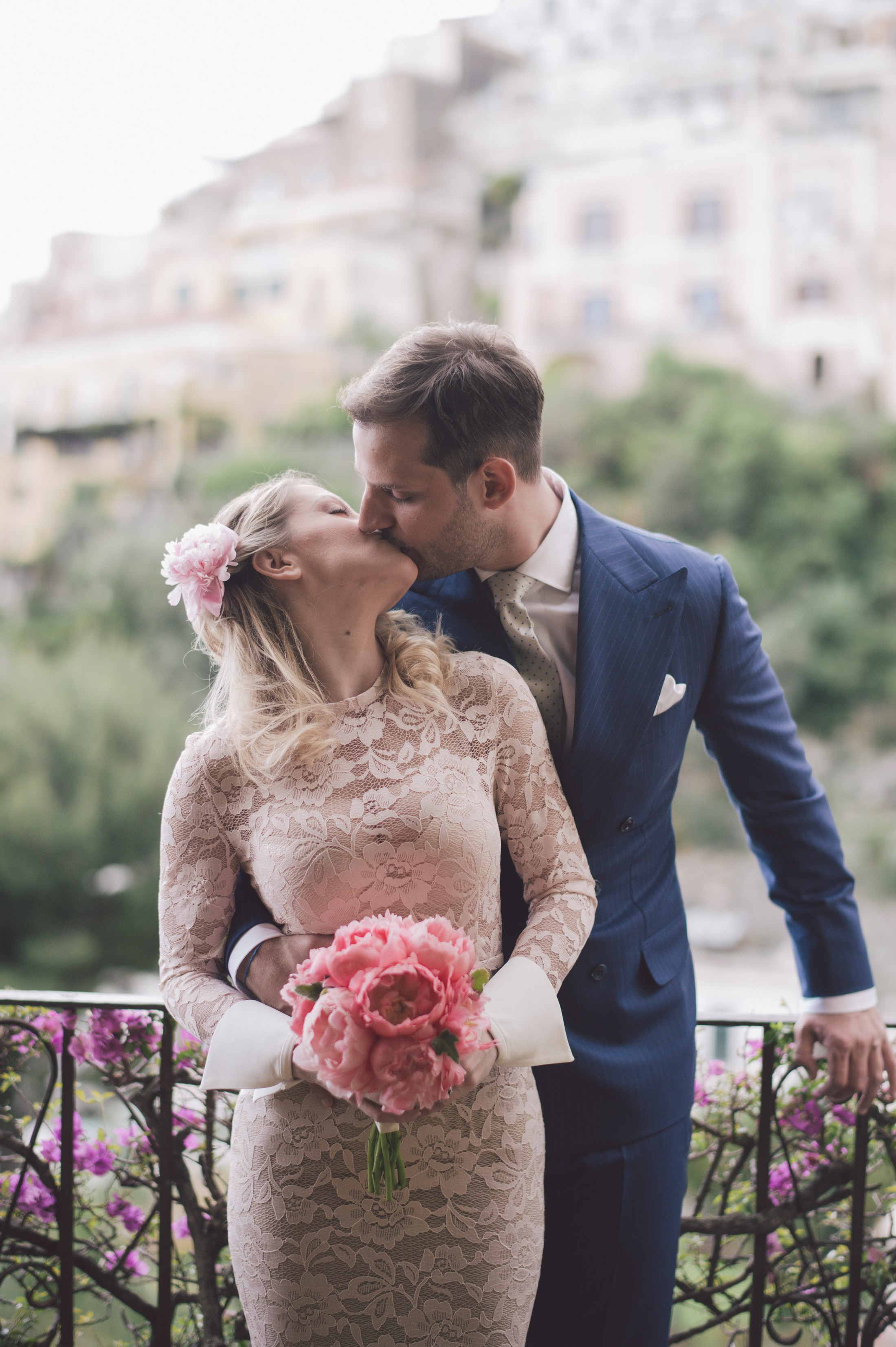 bride and groom kissing on the balcony positano