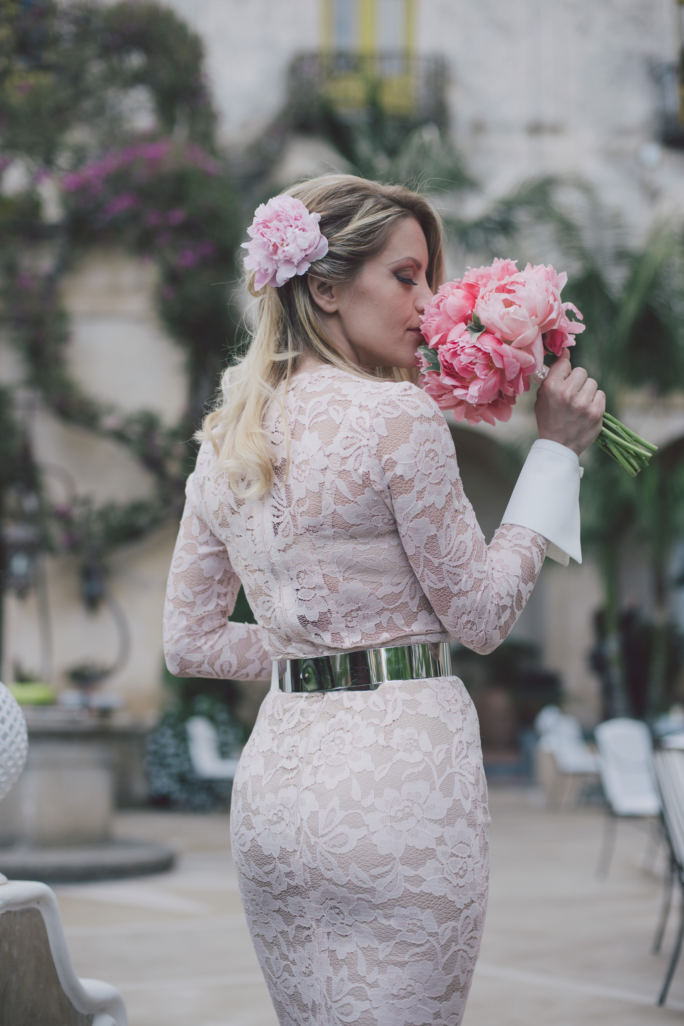 bride smells her pink peony wedding bouquet positano
