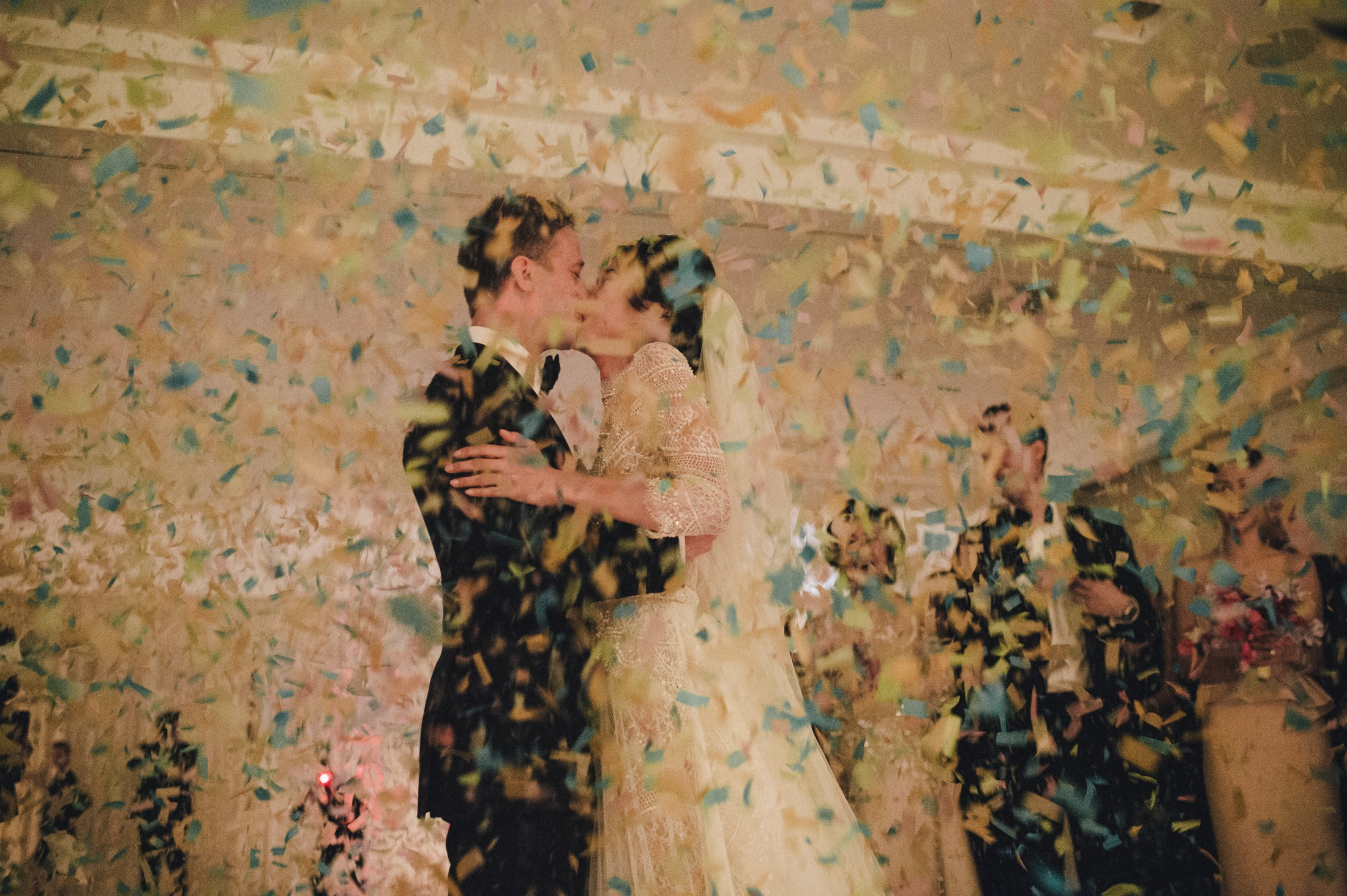bride and groom kissing covered by confetti