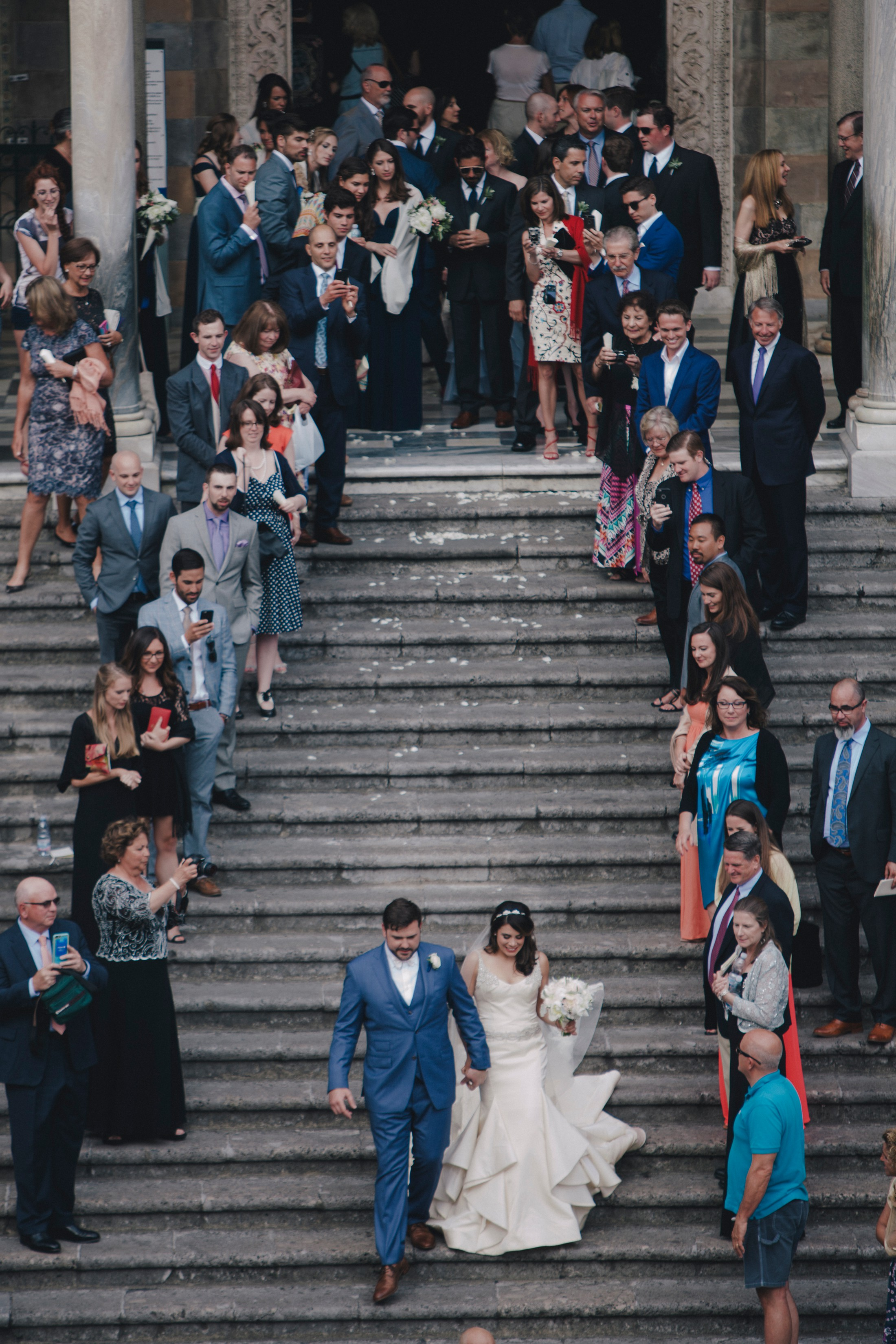 the bride and the groom leave the amalfi cathedral