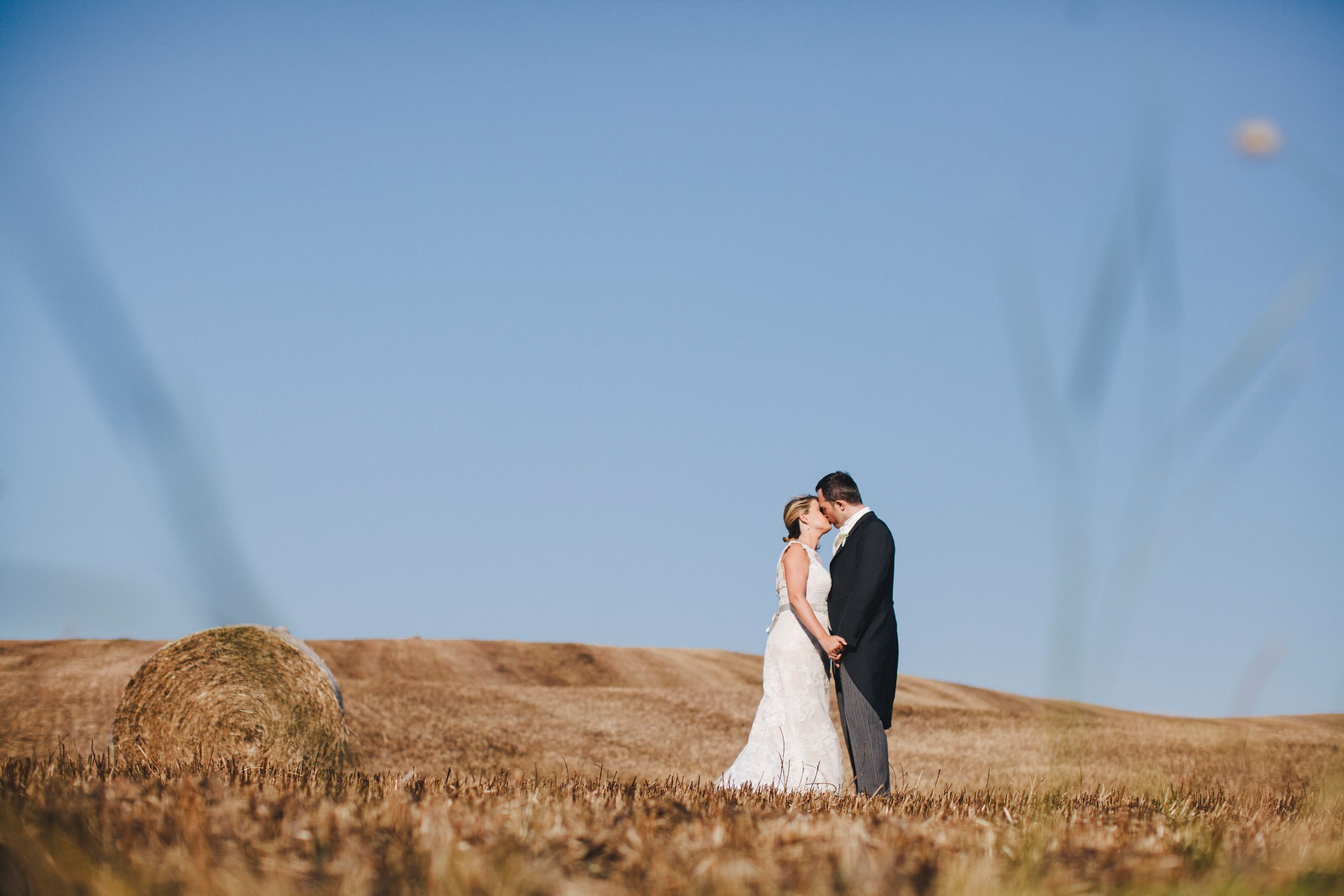 bride and groom kissing with hills behind