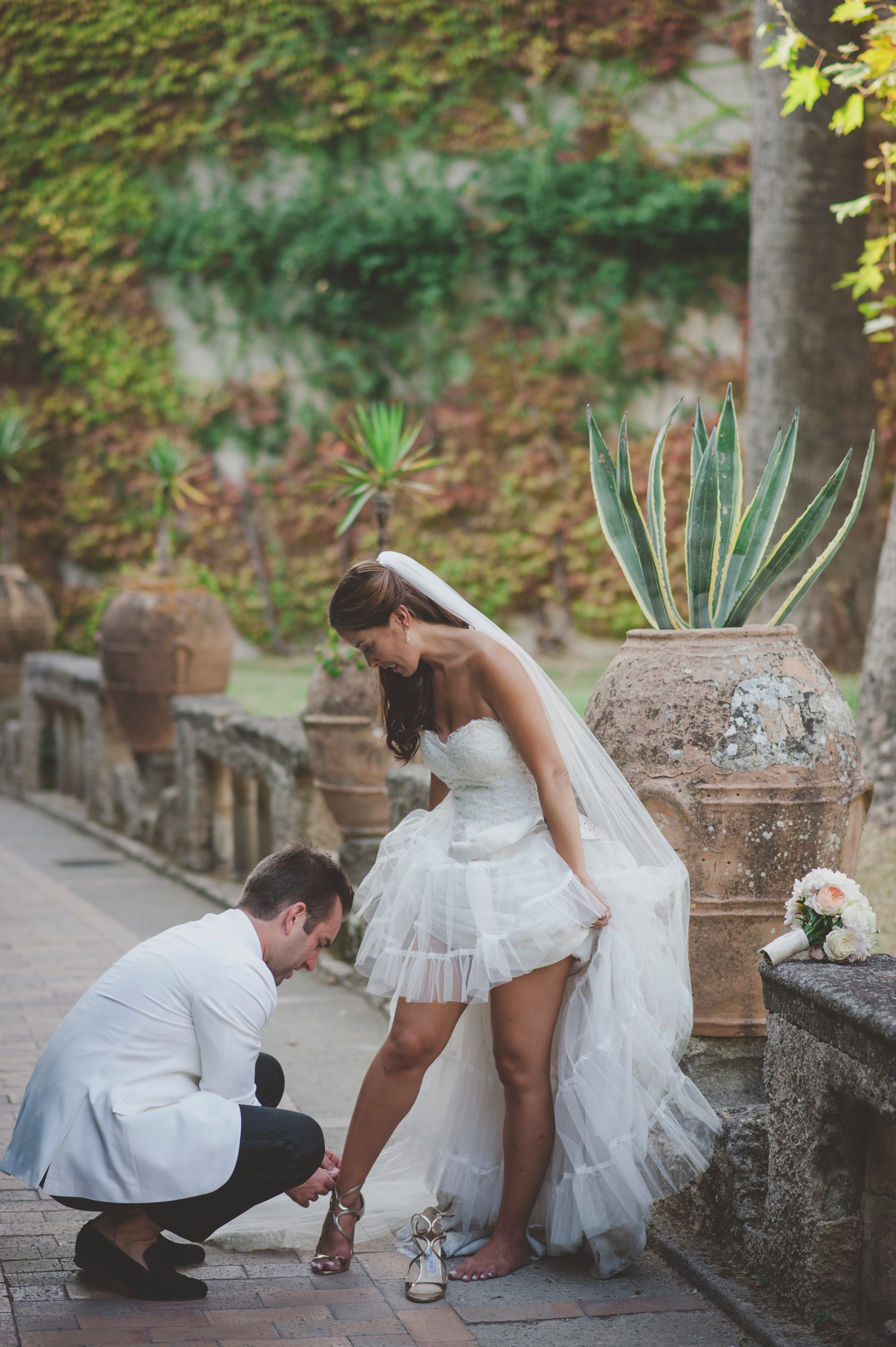 the groom helps the bride with her shoes at villa cimbrone